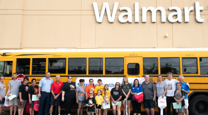 Mayor Hall, Councilmember Duffy, and volunteer residents at the DUSD yellow bus outside Walmart for the Fill the Bus Event.