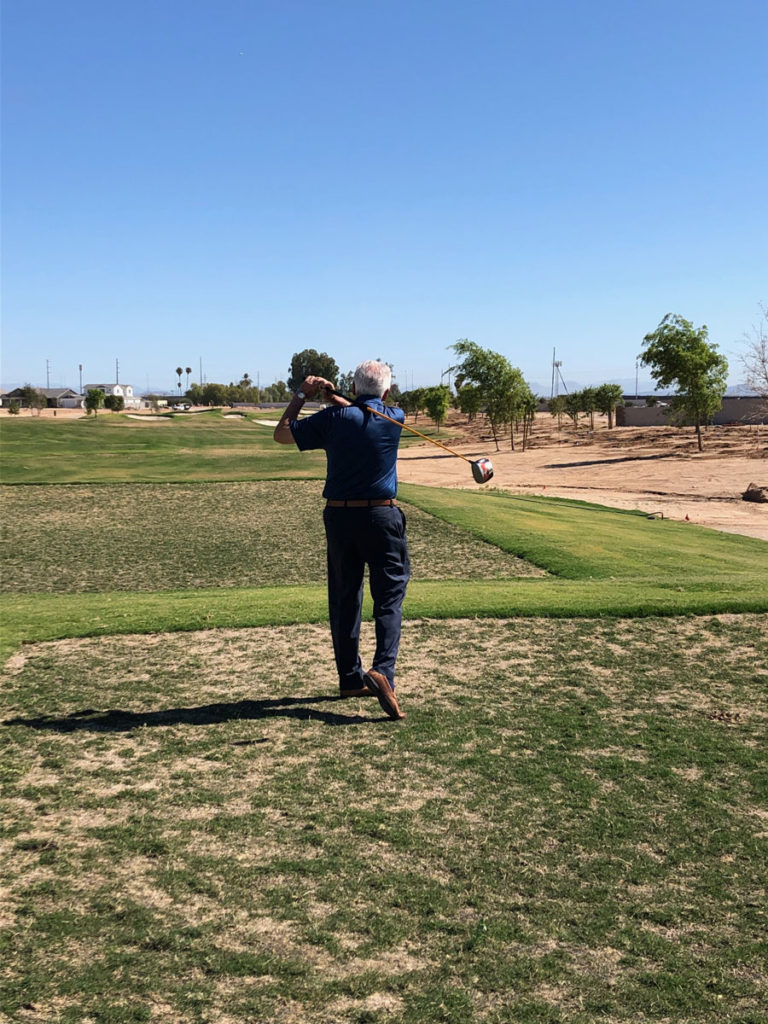 Mayor Hall swings a golf club at the new Toll Brothers gate community golf course.