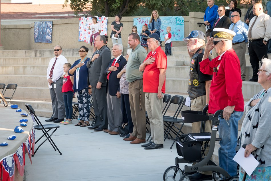 Mayor Hall and Surprise City Councilmembers stand for the pledge of allegiance with other attendees at the DUSD Veterans Appreciation Celebration.