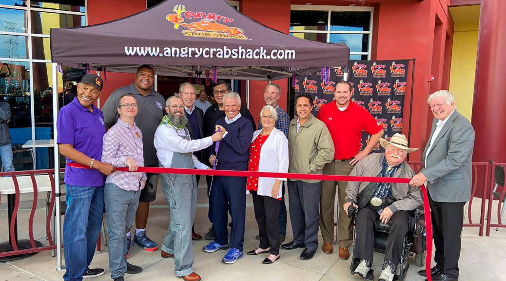 Mayor Hall and the owner of the Angry Crab Shack prepare to cut the ribbon at the restaurant's grand opening event.