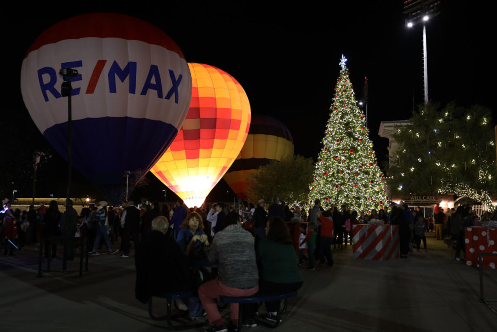 An illuminated Christmas tree and hot air balloons.