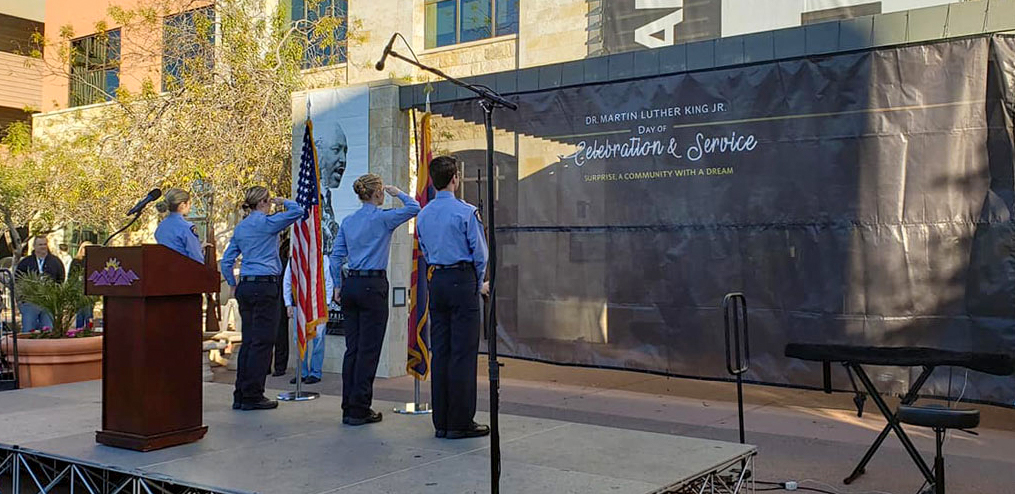 Surprise Police Explorers salute the United States and Arizona flag at the MLK event stage.