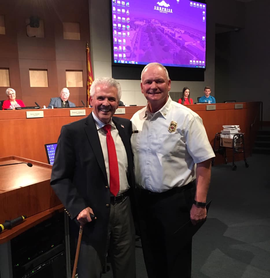 Mayor Hall stands with Surprise Fire-Medical Assistant Chief Darrell Johnston in the council chambers.
