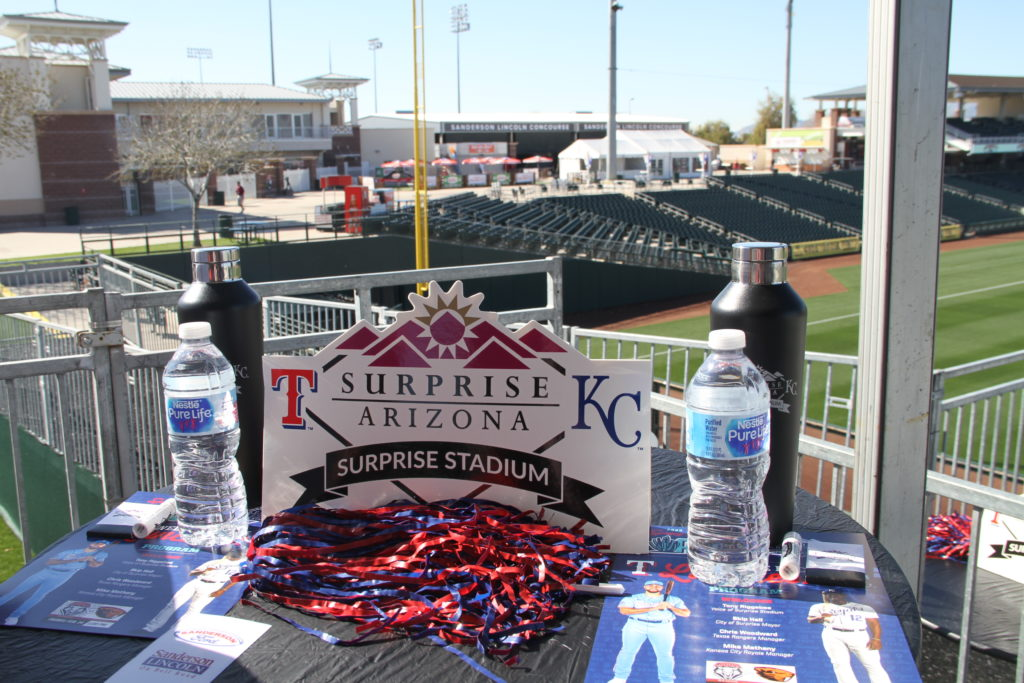 A table at the 2020 Spring Training Welcome Back Lunch with programs, water, Spring Training water bottles and more.