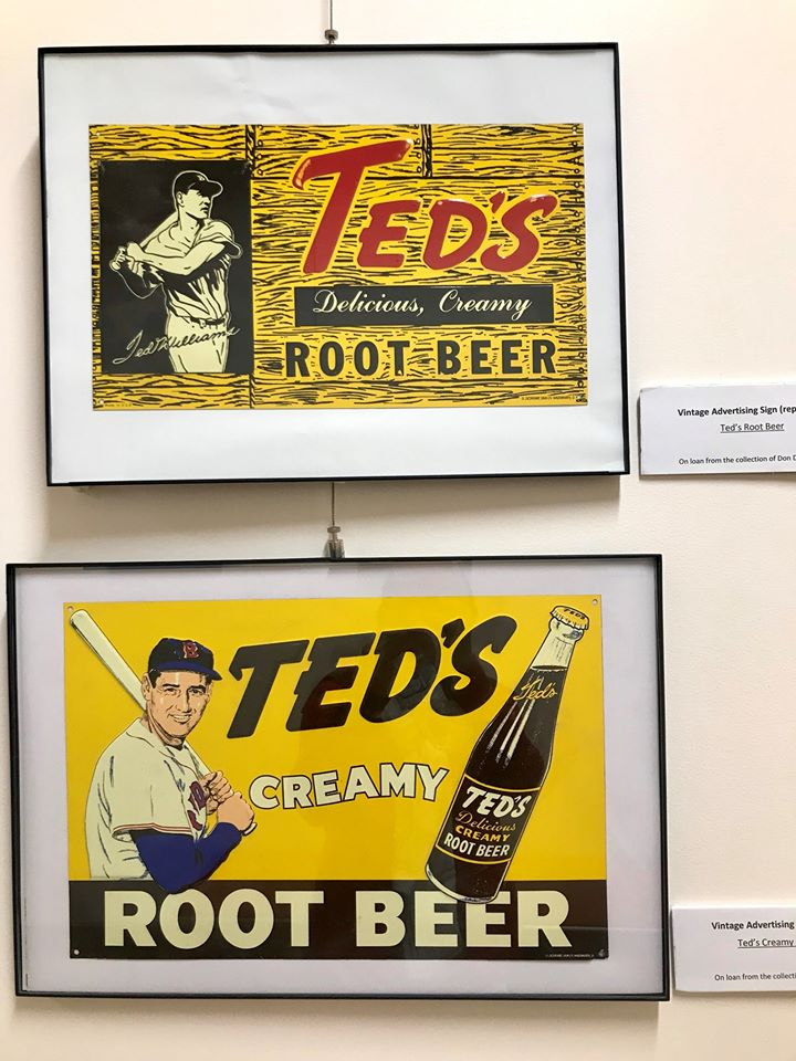 Framed replicas of vintage Ted's Root Beer signs hang on the wall in the City Hall art walk.
