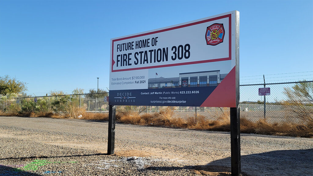 "A sign reading ""Future Home of Fire Station 308"" in front of a fenced plot of land."