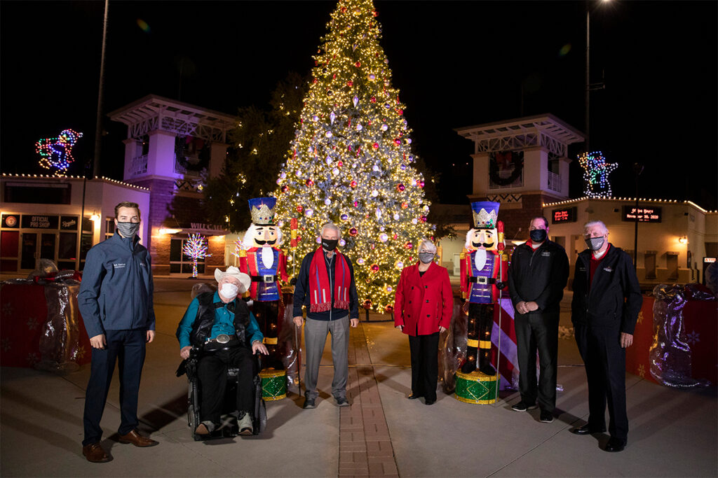 Surprise City Council stands in front of the lit Christmas tree at Surprise Stadium.