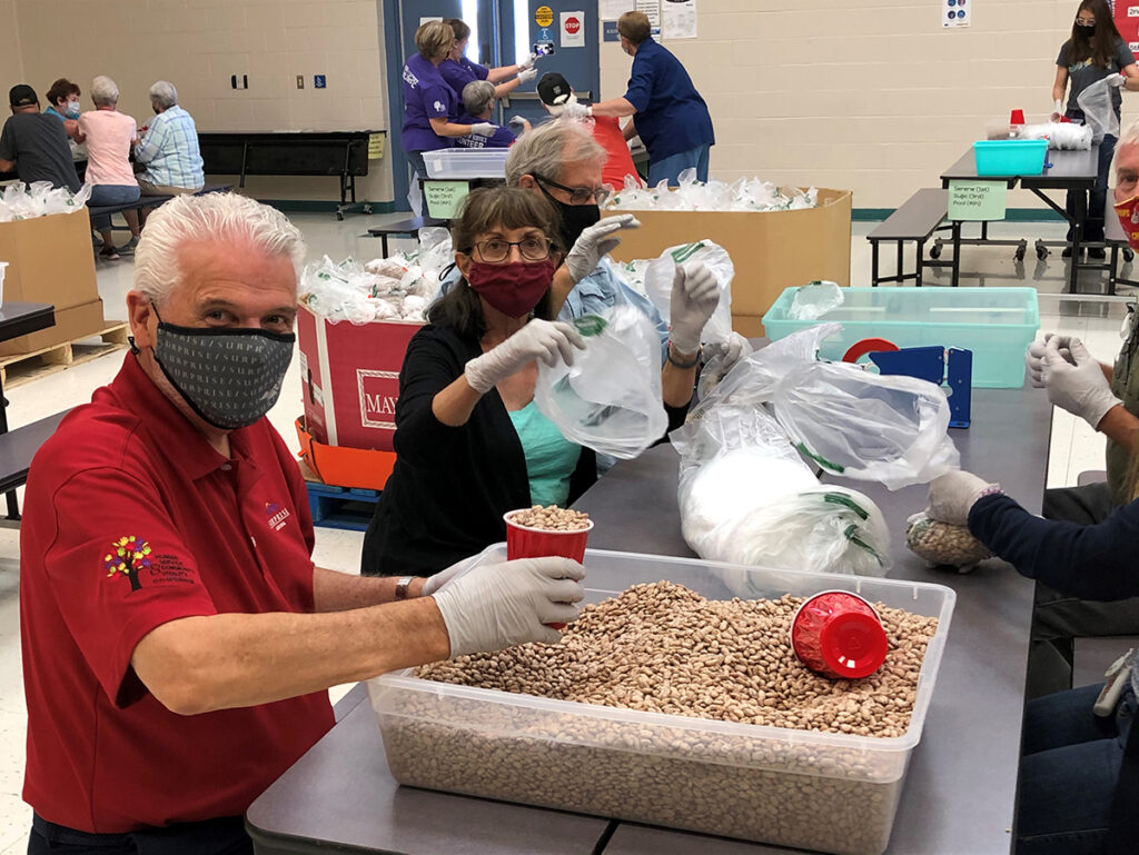 Mayor Hall fills bags with pinto beans.